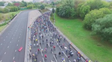 Cyclists ride by speedway turn during bicycle parade