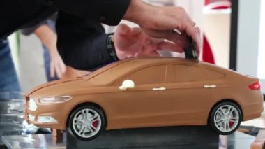 Man smoothing roof of car model