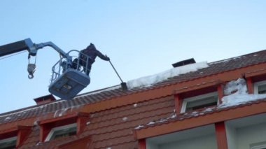 Worker removing snow on the roof of the building