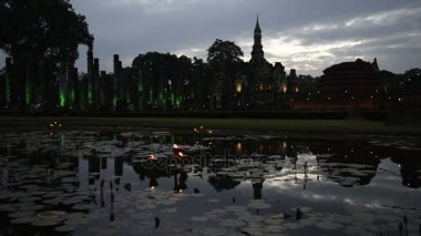 Ruins of Wat Mahathat in lighting in the evening twilight. Sukhothai, Thailand
