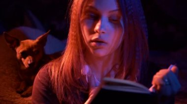 Teen girl reading scary book at night