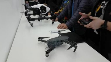 Customers watch quadrocopters at the opening of DJI Store