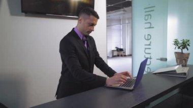 Handsome businessman typing on laptop.
