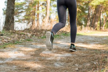 A girl in tights and shoes runs by nature. Sports lifestyle