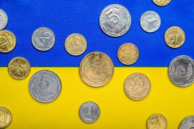 Ukrainian national coins against the background of the national yellow-blue flag. Eurovision currency
