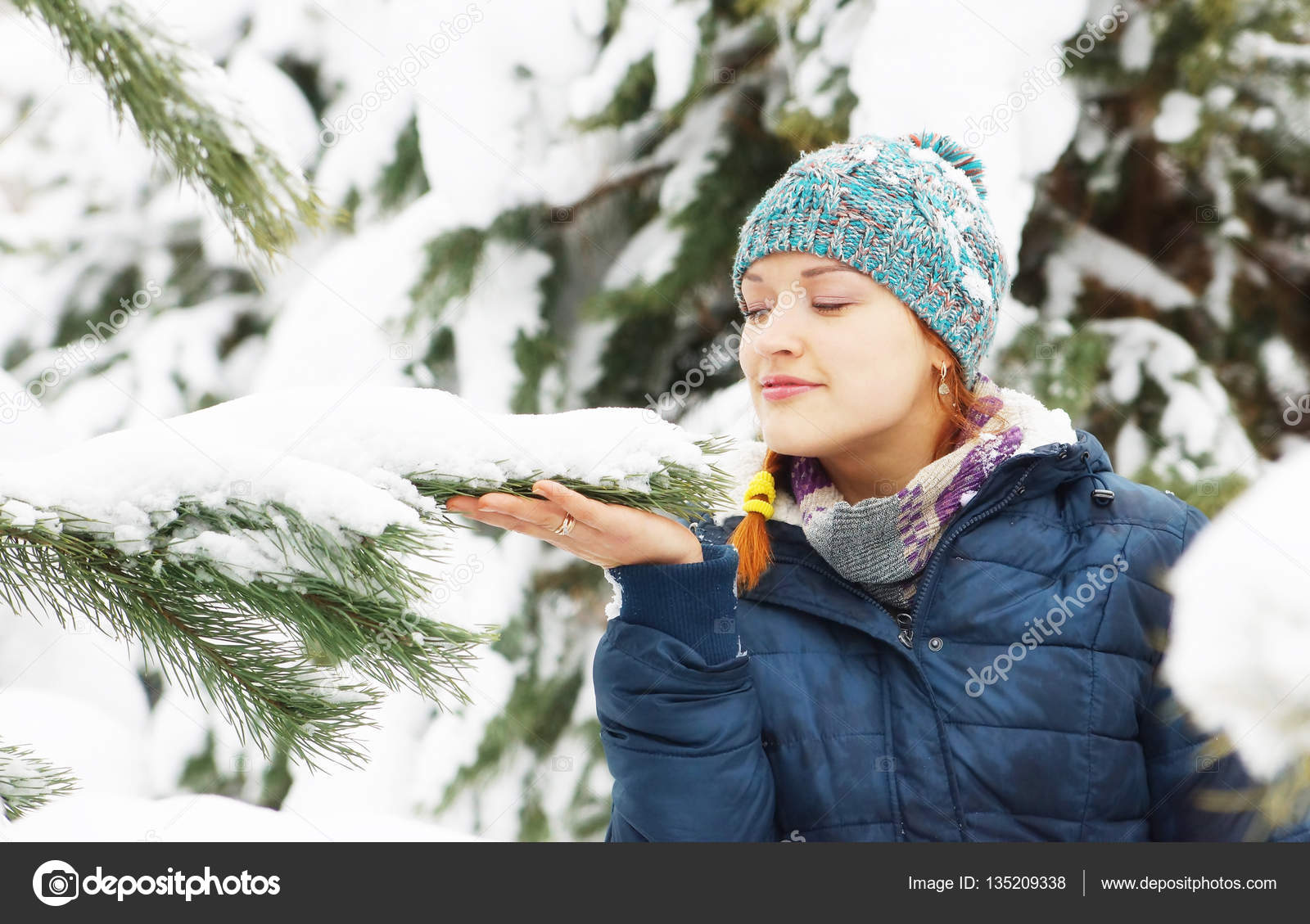 Happy beautiful girl wearing blue jacket stands next to snowy pine