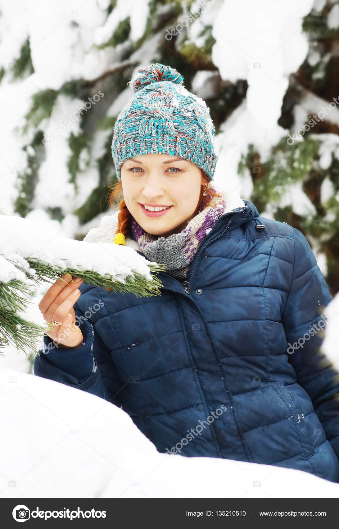 Joyous beautiful girl wearing blue jacket stands next to snowy