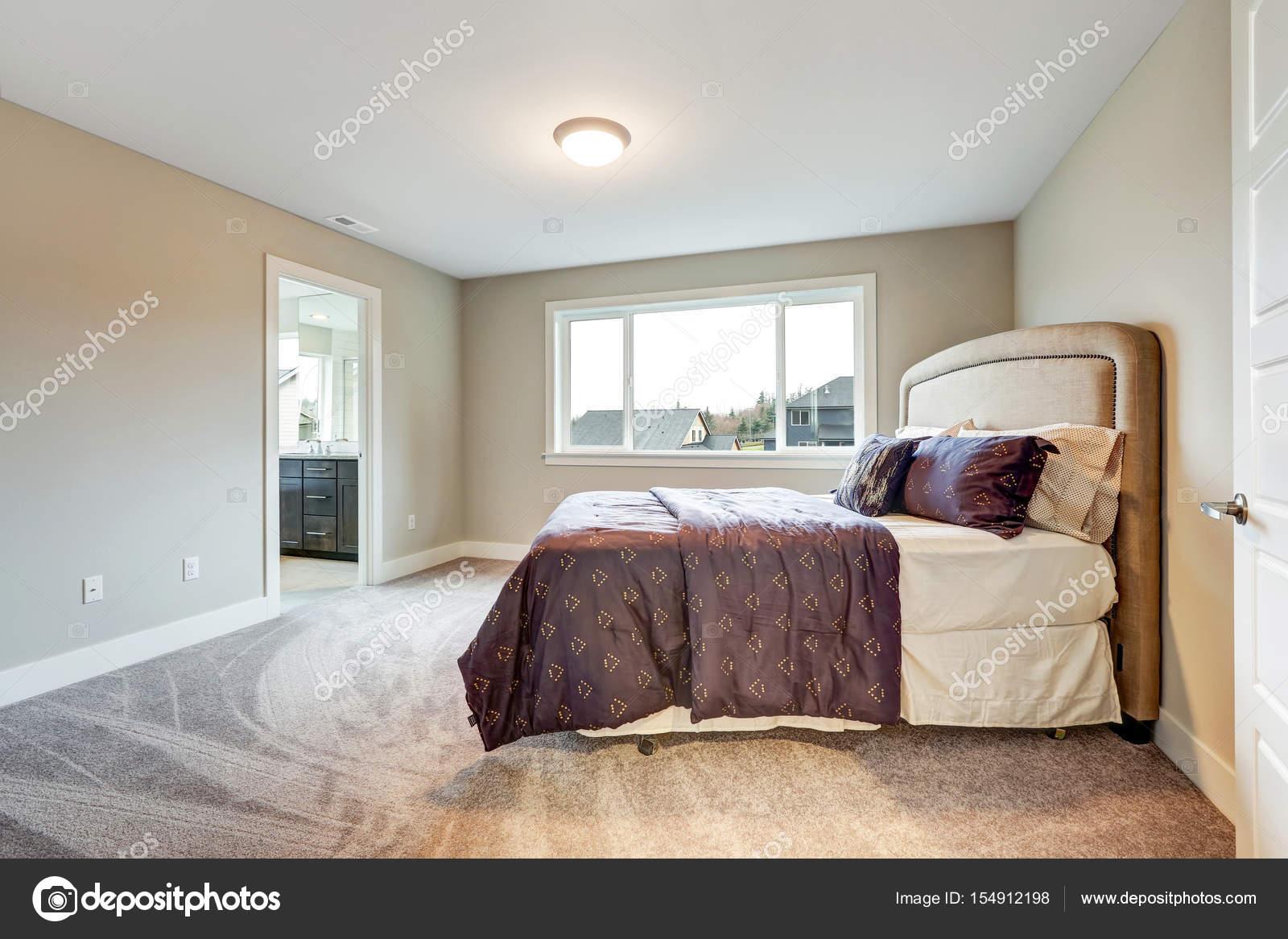 Simple beige camera da letto principale con letto king size letto accentati con testiera imbottita e vestito di marrone biancheria da letto with camera da