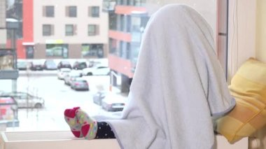 Playful girl with towel on her hair sitting on radiator near window. Snowstorm