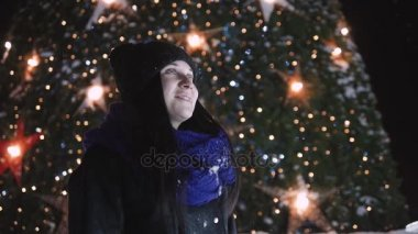 Young Attractive Woman Standing In Front of Shiny Christmas Tree. Woman In Warm Clothes Outside At Night Looking At Camera And Smiling.