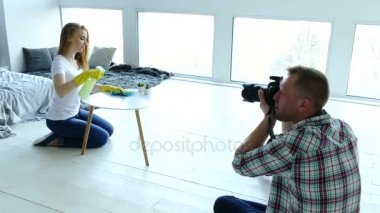 Photo studio backstage . Man photographer work with  woman model like housewife.