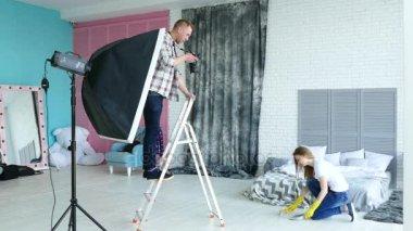 Photostudio backstage . Man photographer explain poses to  woman model like housewife.
