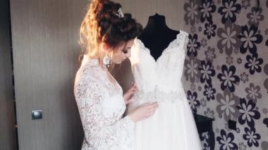 Bride in a boudoir watches her wedding dress