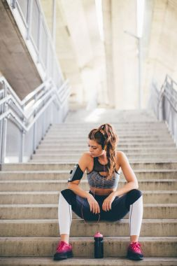 Sports woman sitting on the stairs