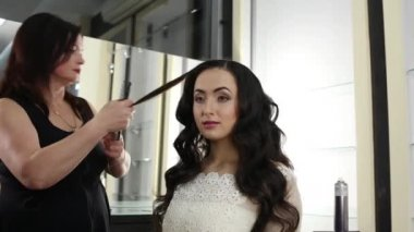 Female hairstylist is making a Chicago waves for a beautiful brunette with long hair
