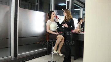 Makeup artist is doing a makeup to dark-haired girl