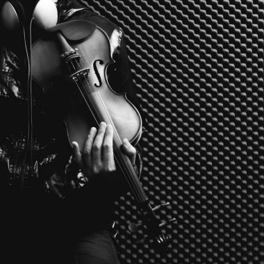 Male musician playing violin in recording studio, black and white