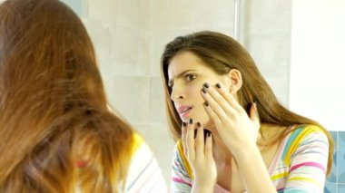 Woman in front of mirror covering pimple with makeup