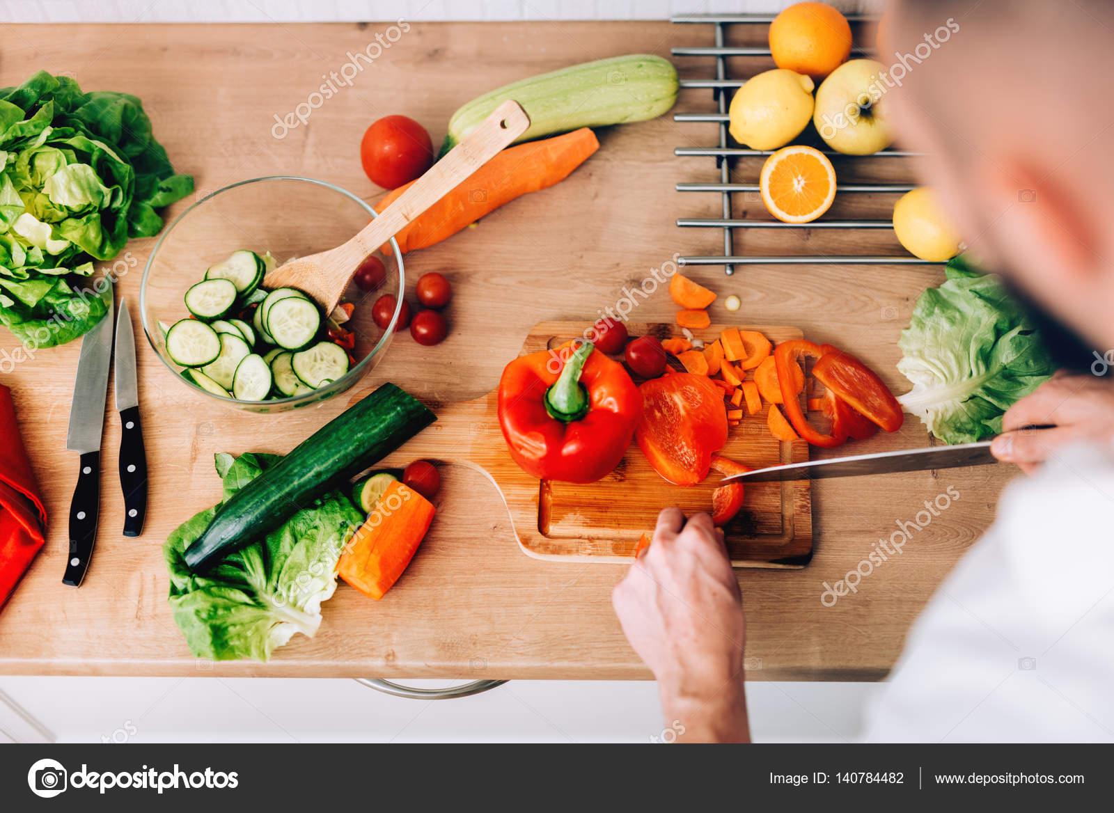 Gut aussehender mann zu hause vorbereiten salat und suppe in modernen küche kochen stockdatei