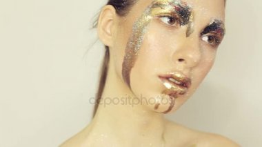 Sensual model with gold make up posing to camera