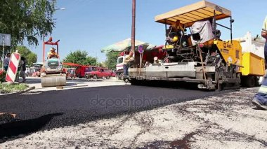 Workers are leveling hot asphalt after is applied on the ground