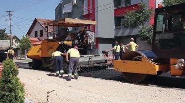 Steamroller is flatting and spreading asphalt after spreader machine.