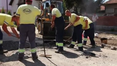 Workers are using shovels for removing excess tarmac, asphalt.