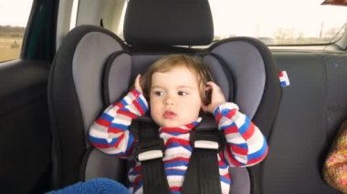 Boy baby kid in a striped jacket in the children's car seat in the car rides. Little baby child infant an automobile armchair