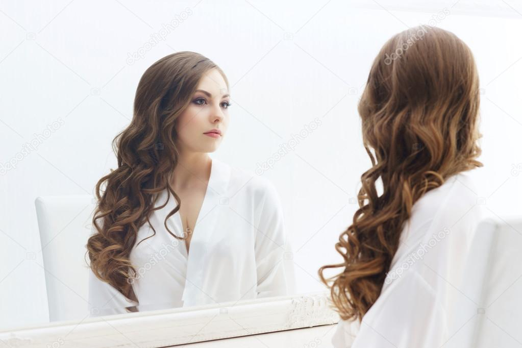 Красивая девушка смотрит в зеркало фото