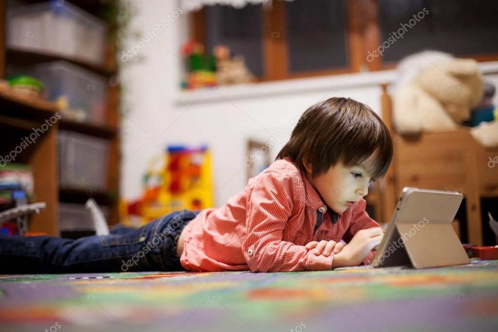 lindo nio tendido en el suelo en la habitacin de los nios jugando en