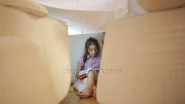 A little girl is sitting in a makeshift house of pillows and a blanket house