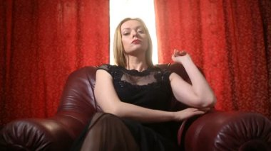 A fatal woman in a black dress and a red lipstick on her lips sits in a leather chair and arrogantly looks into the camera
