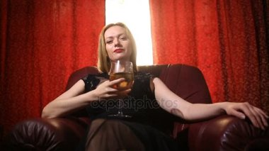 A fatal woman in a black dress and a red lipstick on her lips sits in a leather armchair with a glass of white wine and arrogantly looks into the camera