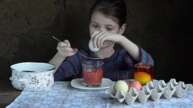 Little girl is painting eggs for Easter