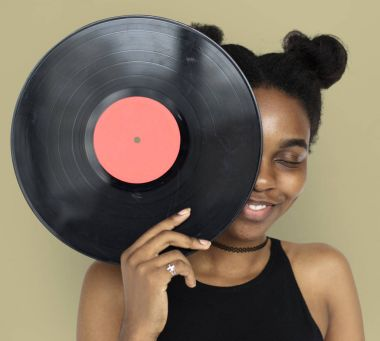 Woman covering face by vinyl record