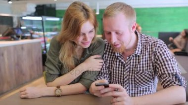 Young couple surfing the web looking at photos on mobile phone