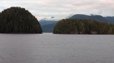 Amazing landscapes on calm water of Pacific on background mountains in Alaska.