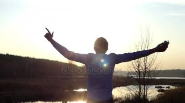 Amazing Sunset and an Energetic Dance of a Young Man on the Bank of a Forest Lake in Early Spring