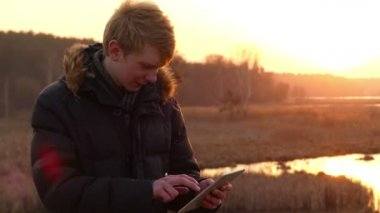 Surprised Young Man is Working on His Tablet Computer With a Touchscreen Display on the Bank of a Forest Lake With a Nice Sunset in Early Spring.