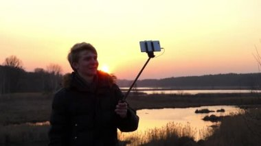 Young Fair Haired Man, Dressed in a Black Anorak, is Taking a Selfie Photo on the Bank of the Forest Lake With a Splendid Sunset