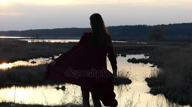 Beautiful Model in Red Dress Twisting and Dancing in Slow Motion at Sunset.