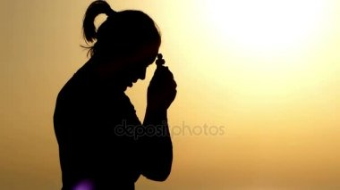 Woman Keeping a Christian Cross in Her Hand at Sunset and Praying.