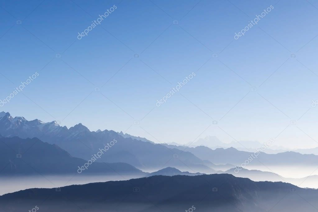 Фотообои Foggy mountain range background with blue sky and white mist in the early morning sun.