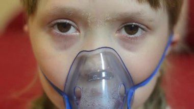 Sad kid in hospital breathing mask for inhalation, girl in hospital is treated by inhalation.