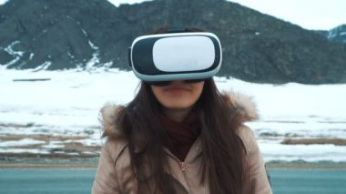A beautiful young girl or teenager uses virtual reality glasses.