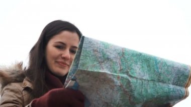 Young tourist woman exploring Mountain map while traveling in mountains in winter, vacation concept