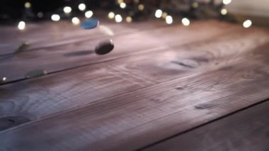 Pile of coins falling on the wooden table