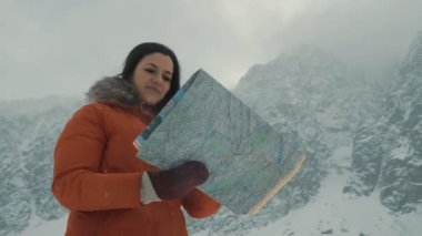 The girl is studying a map against the background of snow-capped mountains