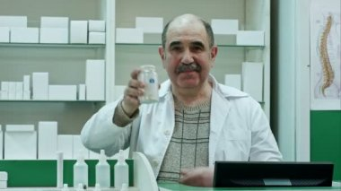 Smiling doctor holding up a bottle of tablets or pills with a blank white label for treatment of an illness and look to a camera