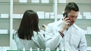 Female and male pharmacists working in pharmacy, talking via smart phone and checking pills